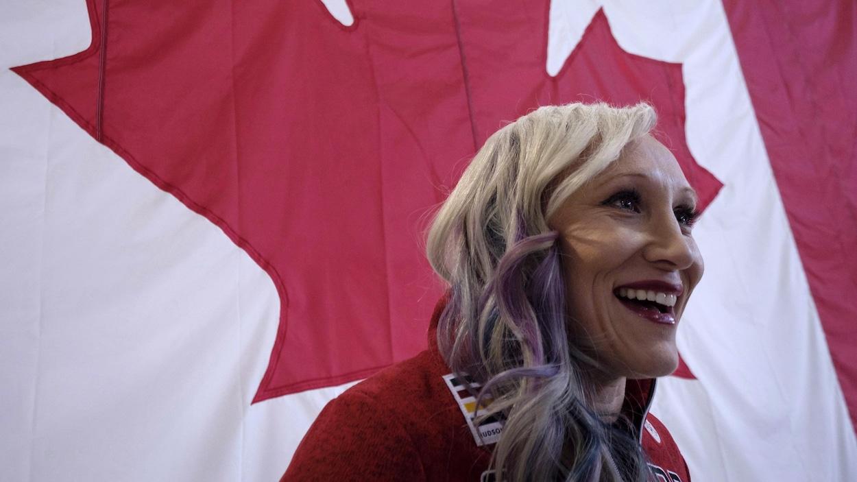 Une athlète sourit devant un drapeau canadien