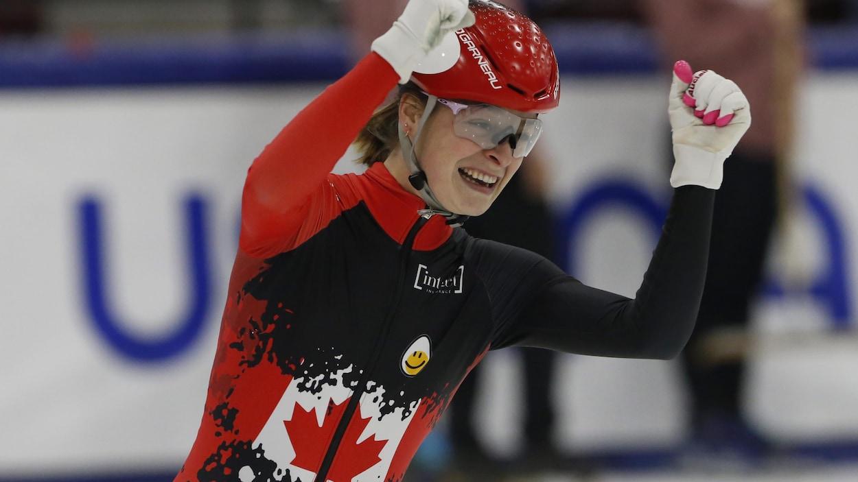 Une patineuse lève ses bras en triomphe.