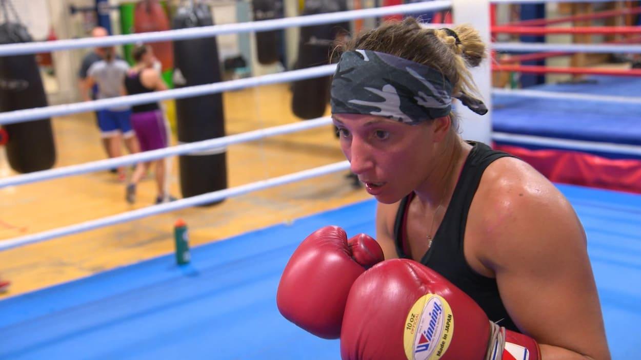 Une boxeuse à l'entraînement sur un ring