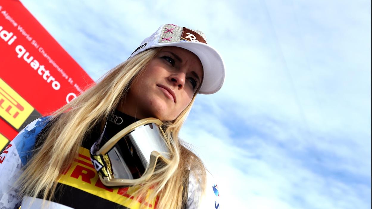 Lara Gut regarde au loin après le Super G féminin des Championnats du monde, en février 2017, à St-Moritz. Elle porte une casquette et a ses lunettes de ski au cou.