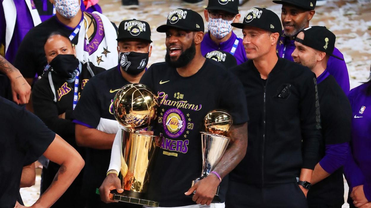 Un homme porte deux trophées dans ses mains.