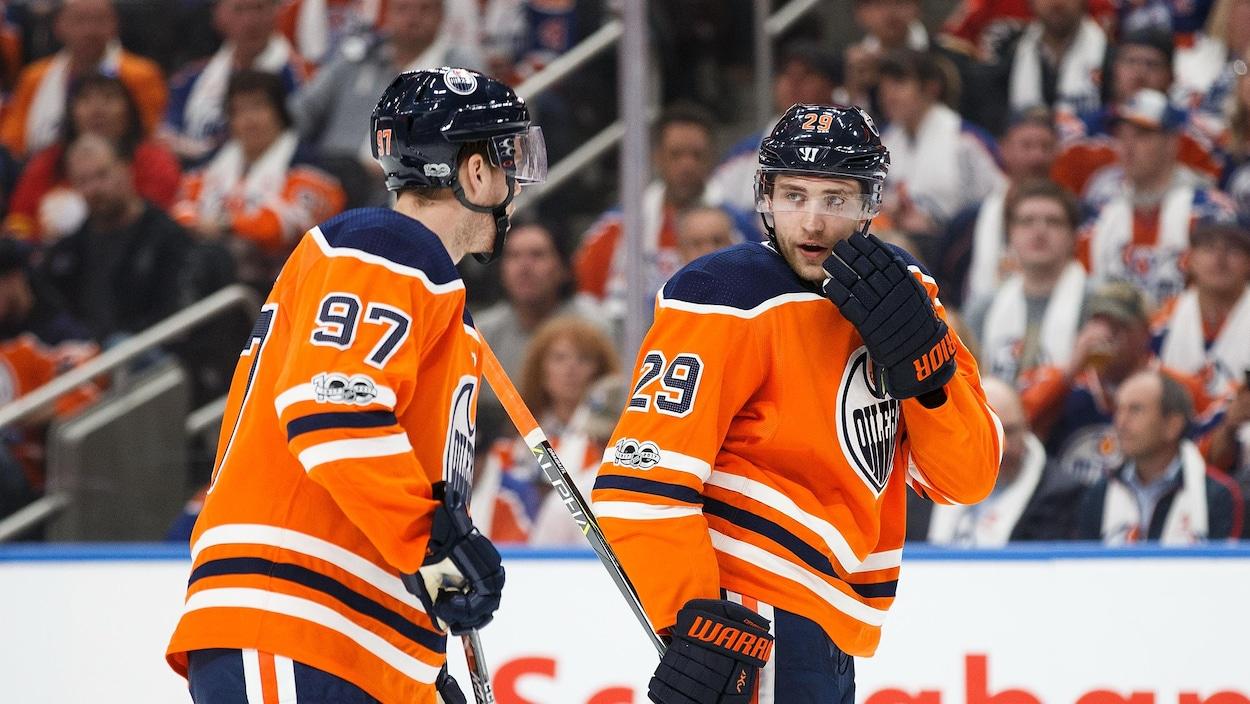 Connor McDavid et Leon Draisaitl des Oilers discutent stratégie lors d'un match face aux Flames