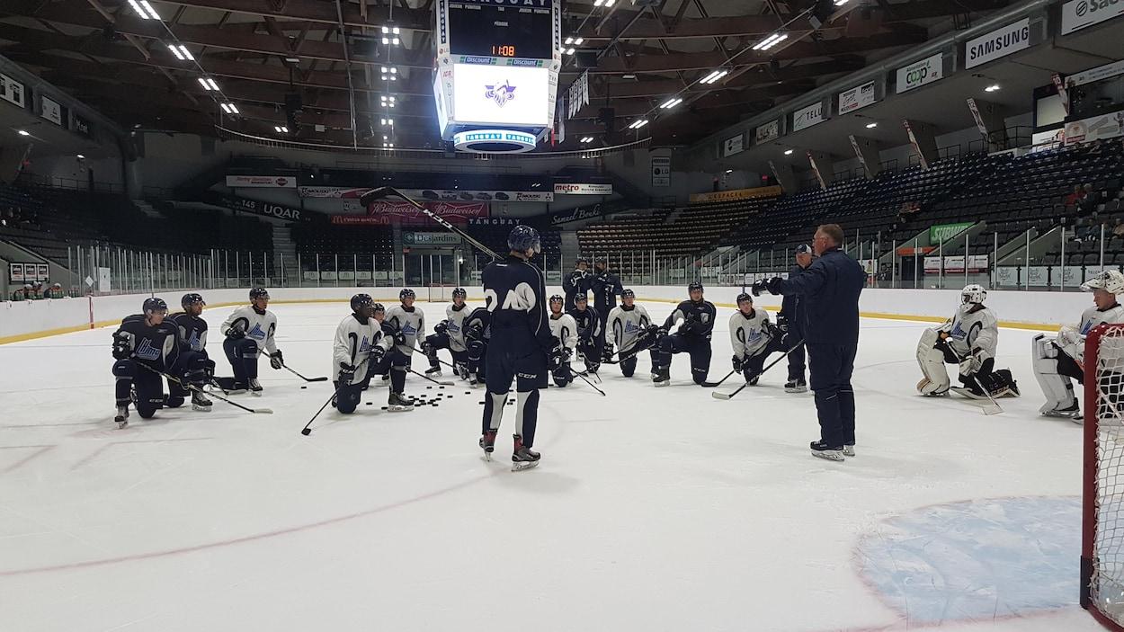 Joueurs et entraîneurs de l'Océanic de Rimouski sur la patinoire du Colisée Financière Sun Life