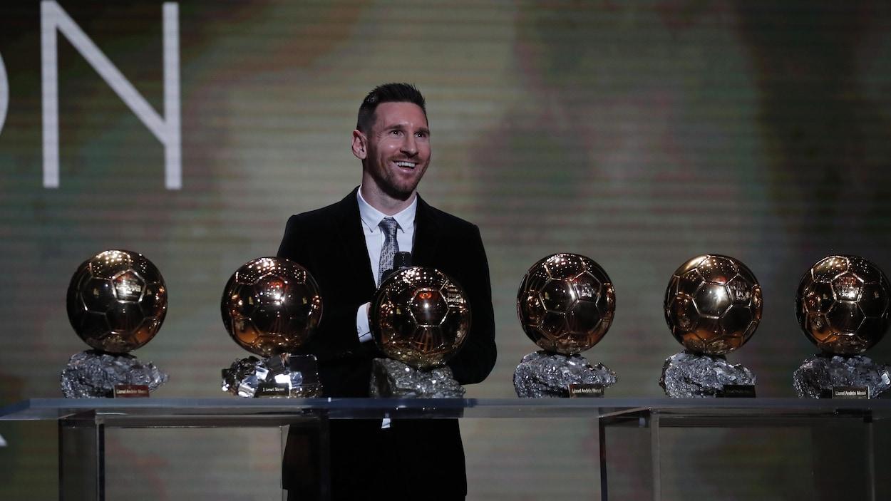 Il sourit devant ses trophées.