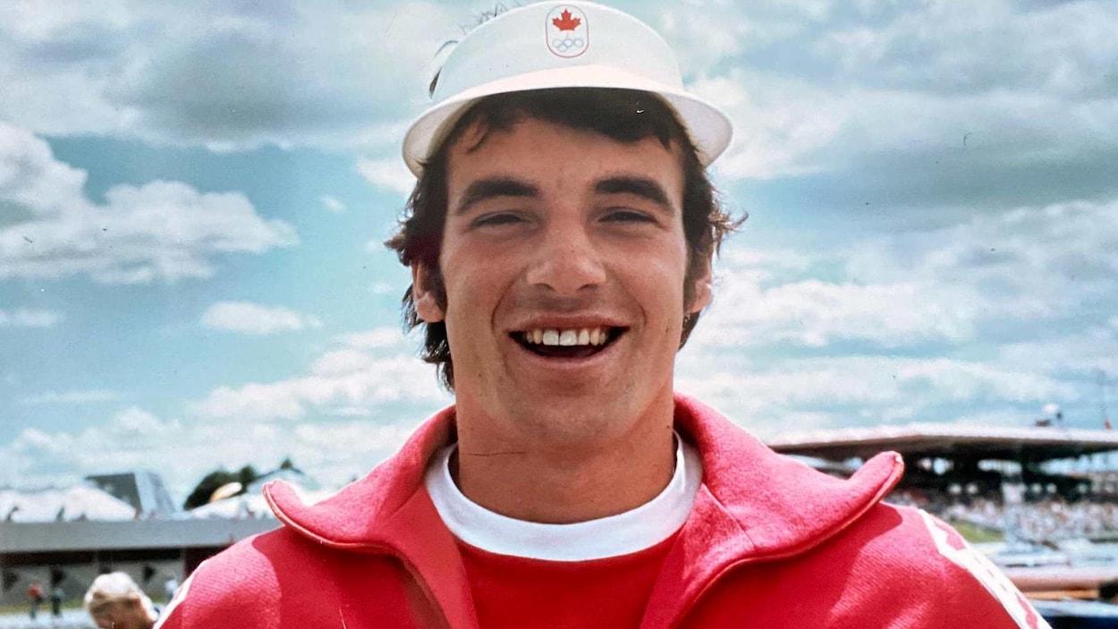 Il sourit et arbore une veste et chapeau aux couleurs de l'équipe canadienne.