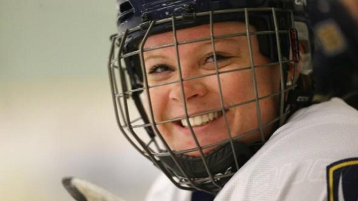 Une joueuse de hockey souriante porte un casque muni d'une grille.