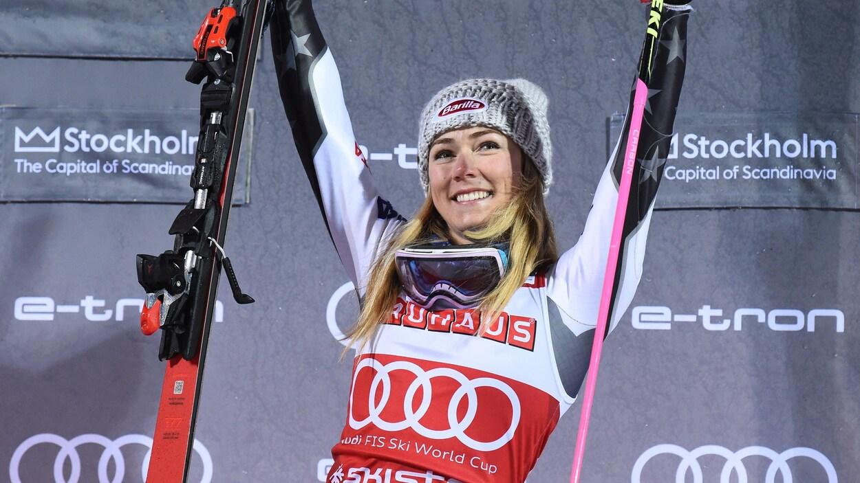 Elle tient un ski dans chaque main.
