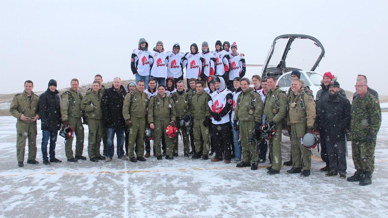 Des membres des Snowbirds posent avec des joueurs des Warriors devant un avion en plein hiver.