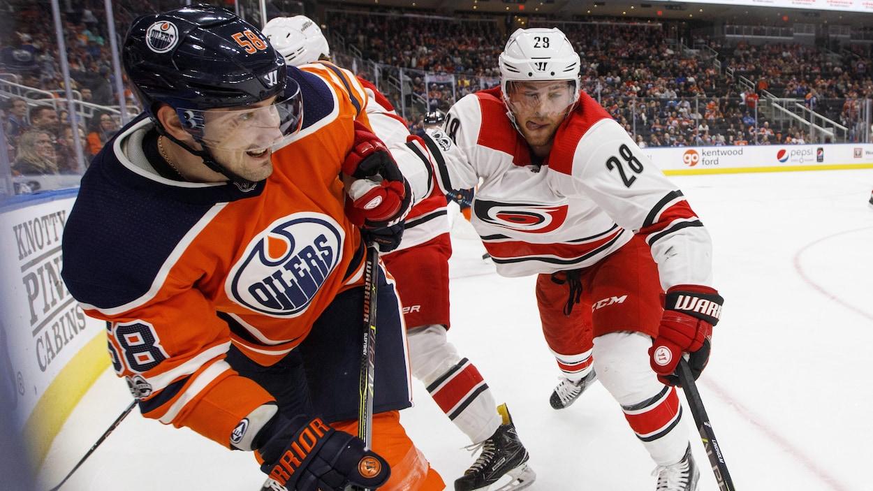 Elias Lindholm pousse Anton Slepyshev dans le coin de la patinoire.
