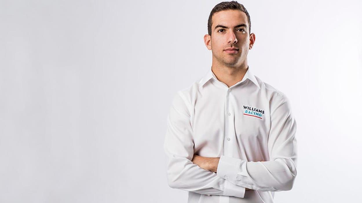 Il porte une chemise aux couleurs de Williams et croise les bras.