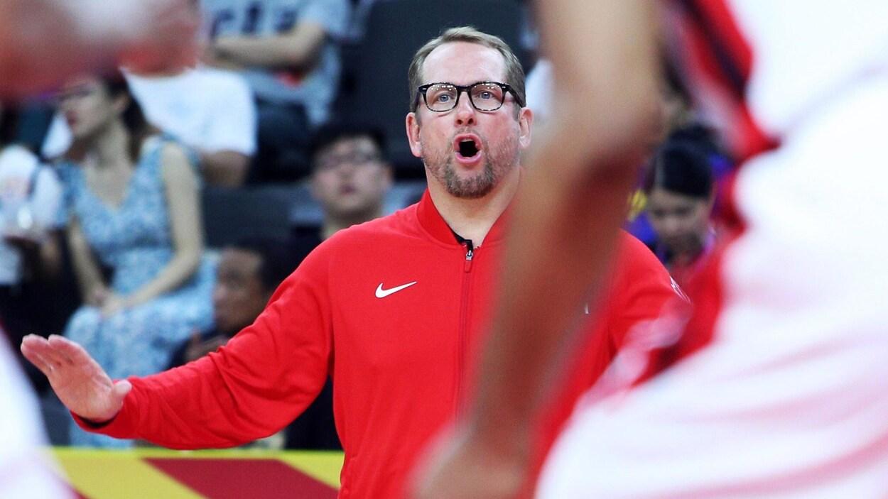Debout sur les lignes de côté, il dirige les joueurs sur le parquet de basketball.