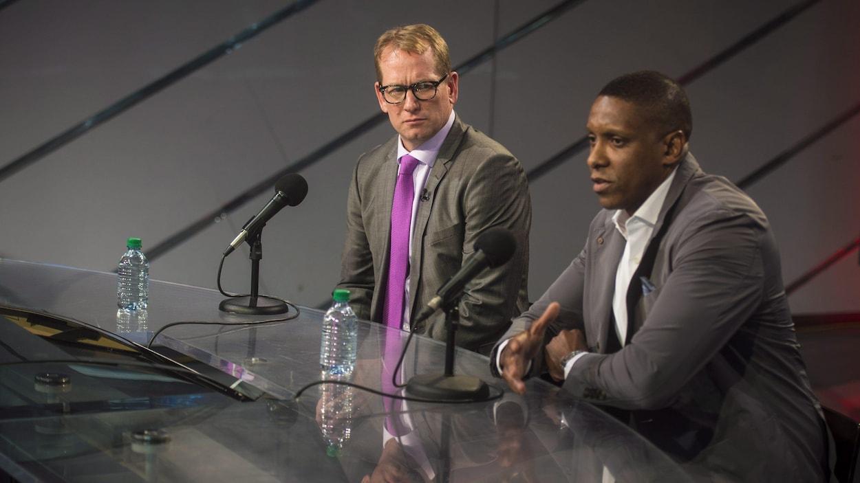 Nick Nurse écoute parler Masai Ujiri, président des Raptors de Toronto, lors de sa présentation comme entraîneur-chef.