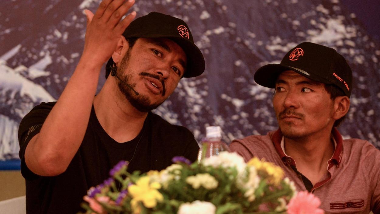 L'alpiniste Nirmal Purja lève la main pour expliquer son point sous les yeux de son sherpa Mingma David lors d'une conférence de presse
