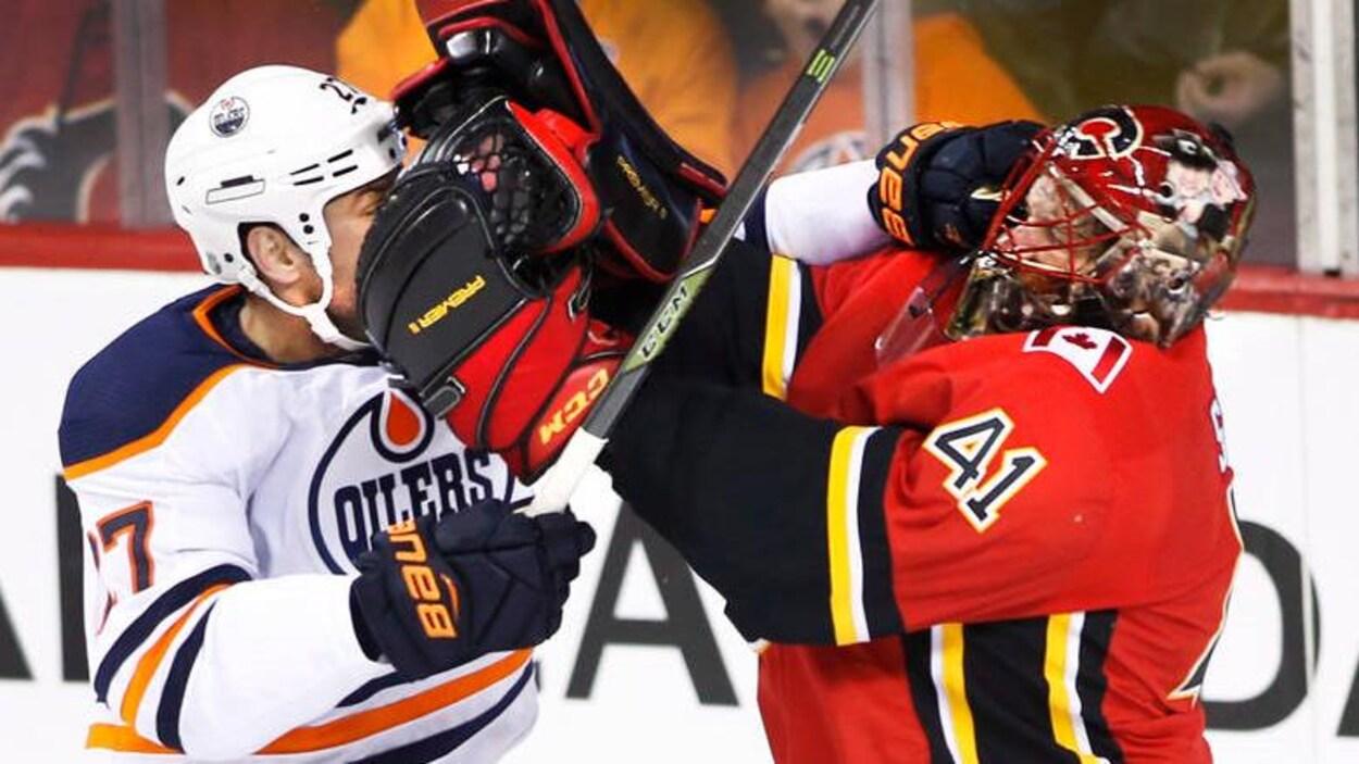 Altercation sur la glace entre deux joueurs : à g., des Oilers, et à d. des Flames