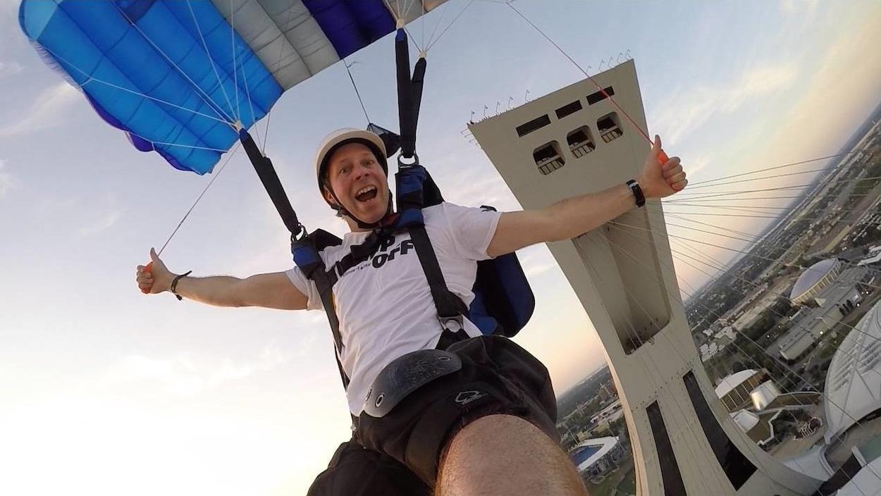 Il sourit tout en manipulant son parachute.