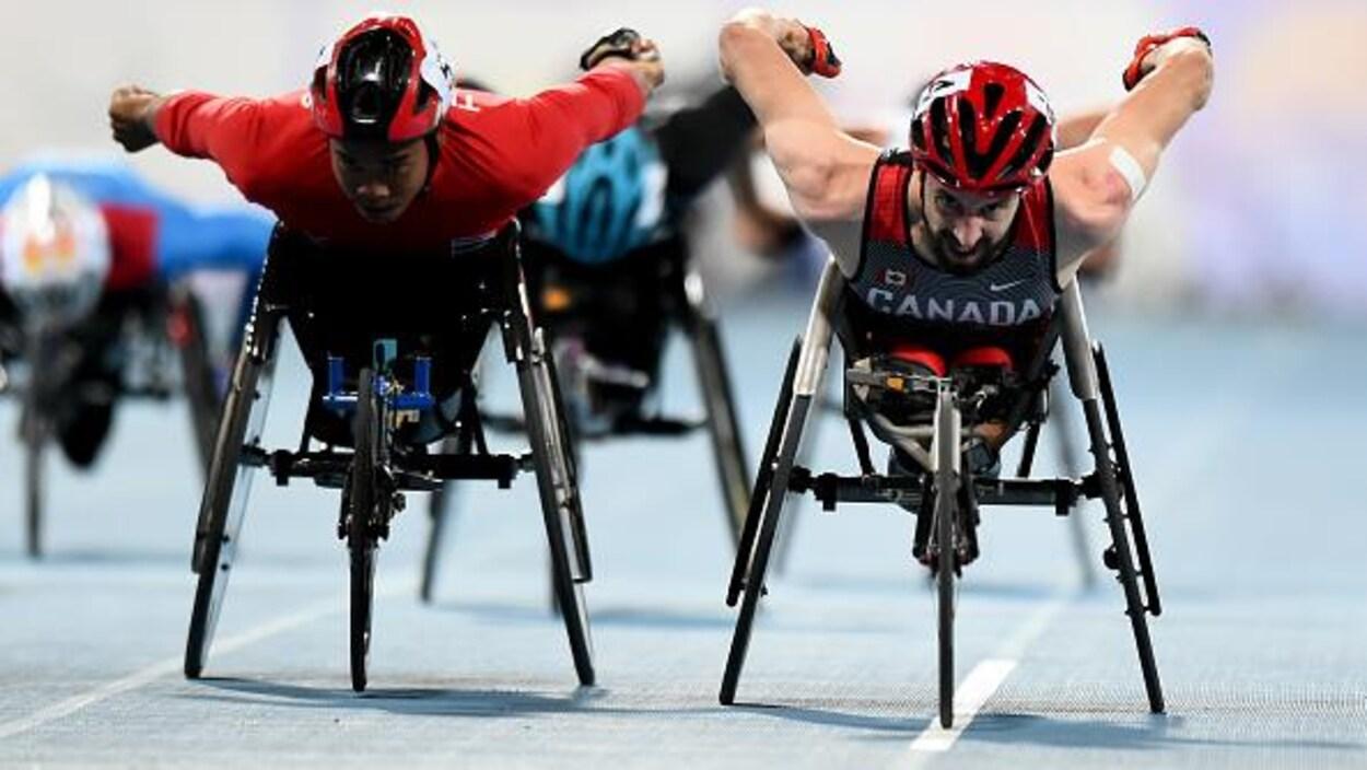 Deux adversaires sprintent côte à côte en fauteuil roulant.