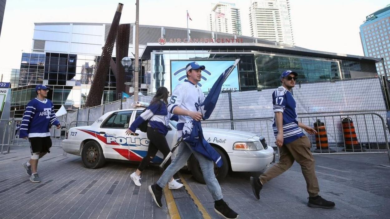 Des partisans des Maple Leafs devant une voiture de police.