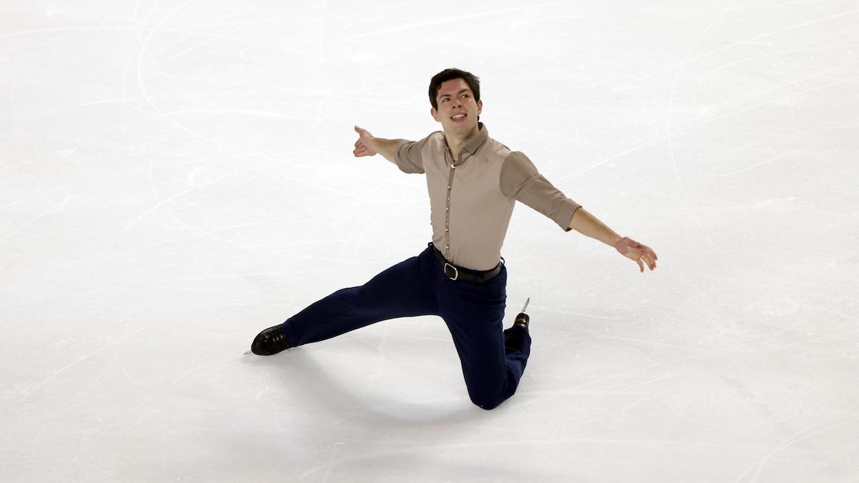 Un genou sur la glace, il étend les bras.