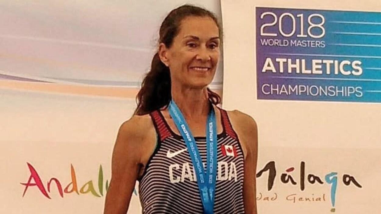 Patty Blanchard est sur le podium avec une médaille d'or au cou et un certificat attestant sa performance.