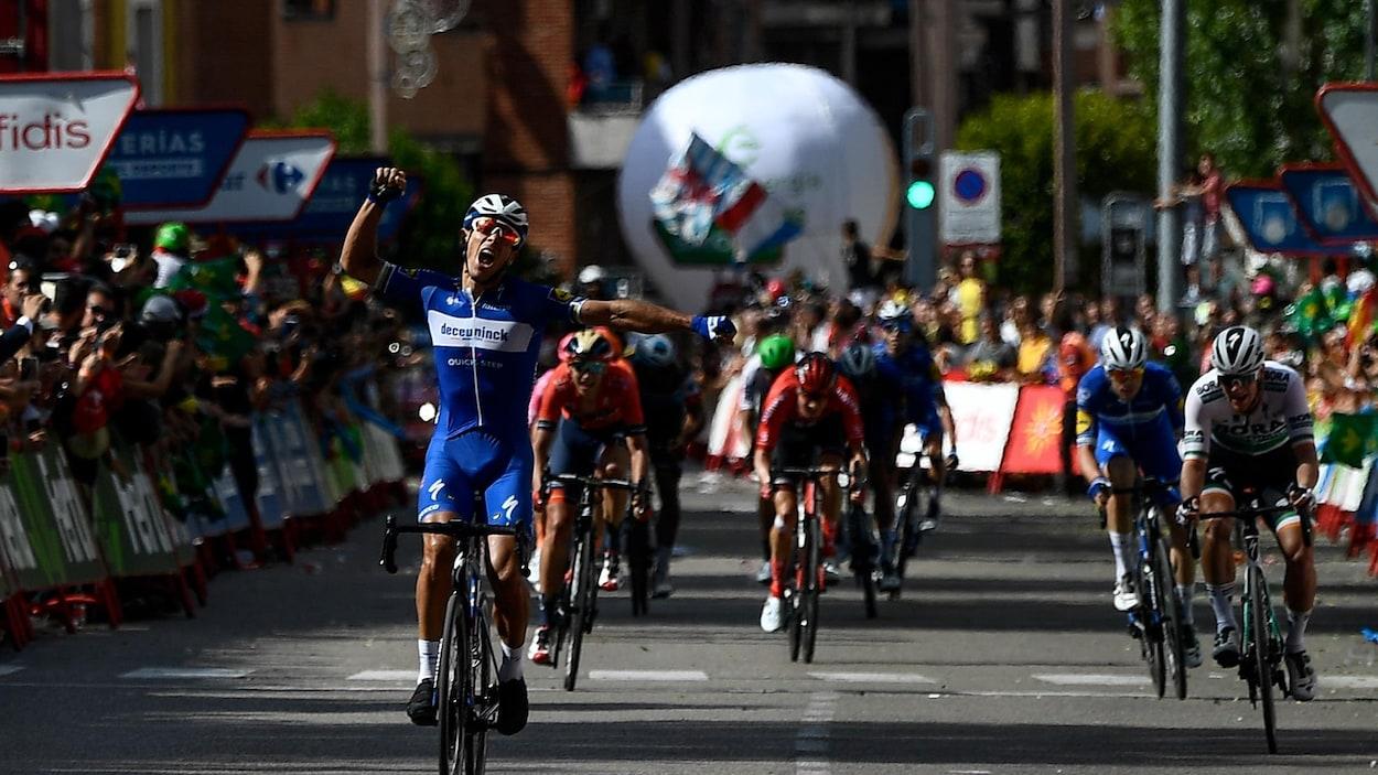 Un cycliste lève les bras en triomphe devant des adversaires qu'il vient de devancer au sprint.