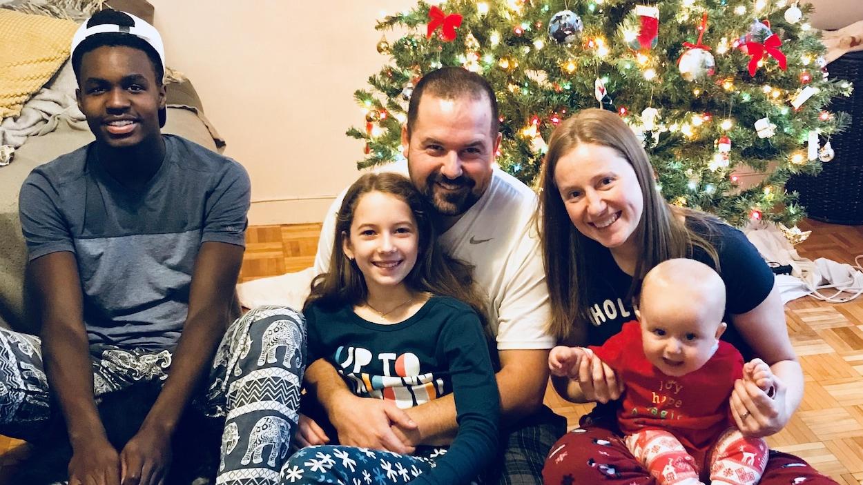 Prinzy Dessources et sa nouvelle famille sont assis sur le plancher devant leur arbre de Noël.
