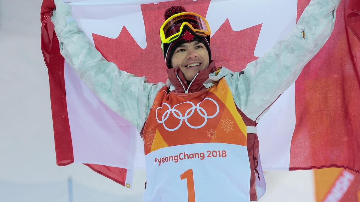 Mikaël Kingsbury célèbre sa victoire avec un drapeau canadien