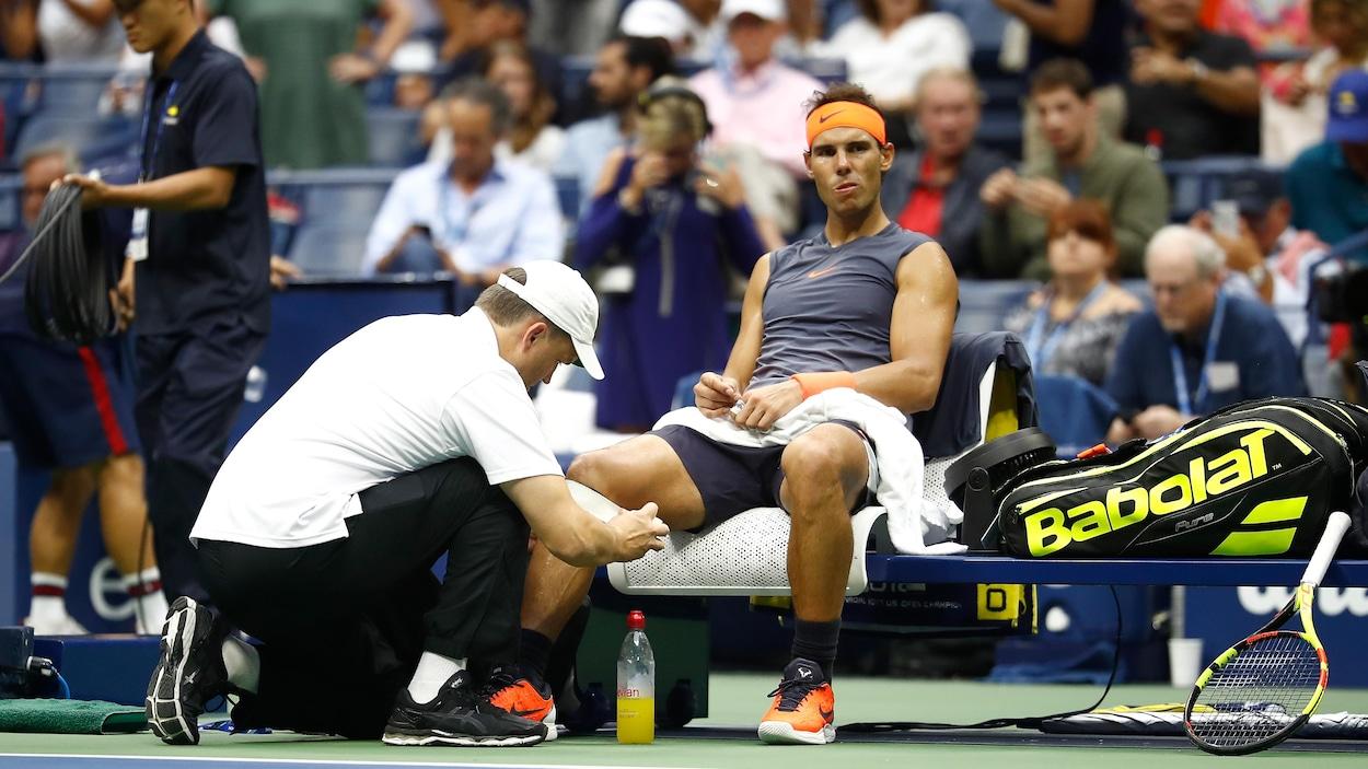 Rafael Nadal, assis, reçoit des traitements au genou.