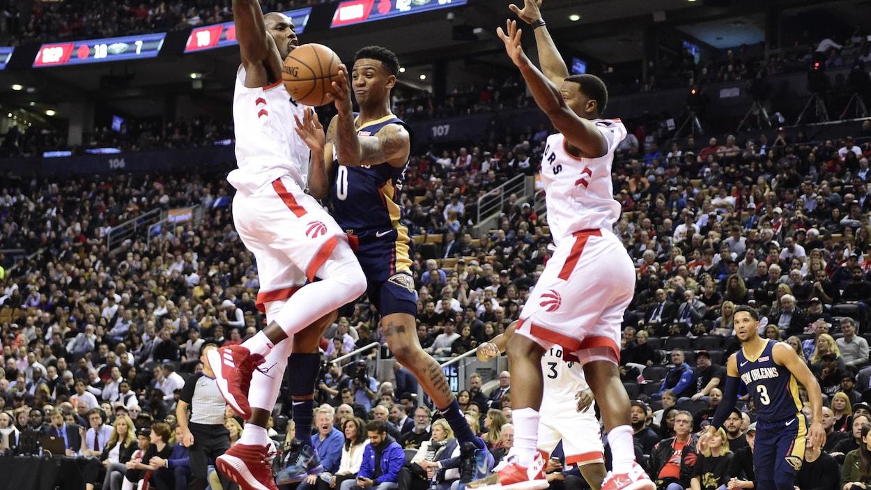 Deux joueurs tentent de freiner la progression au panier d'un adversaire.