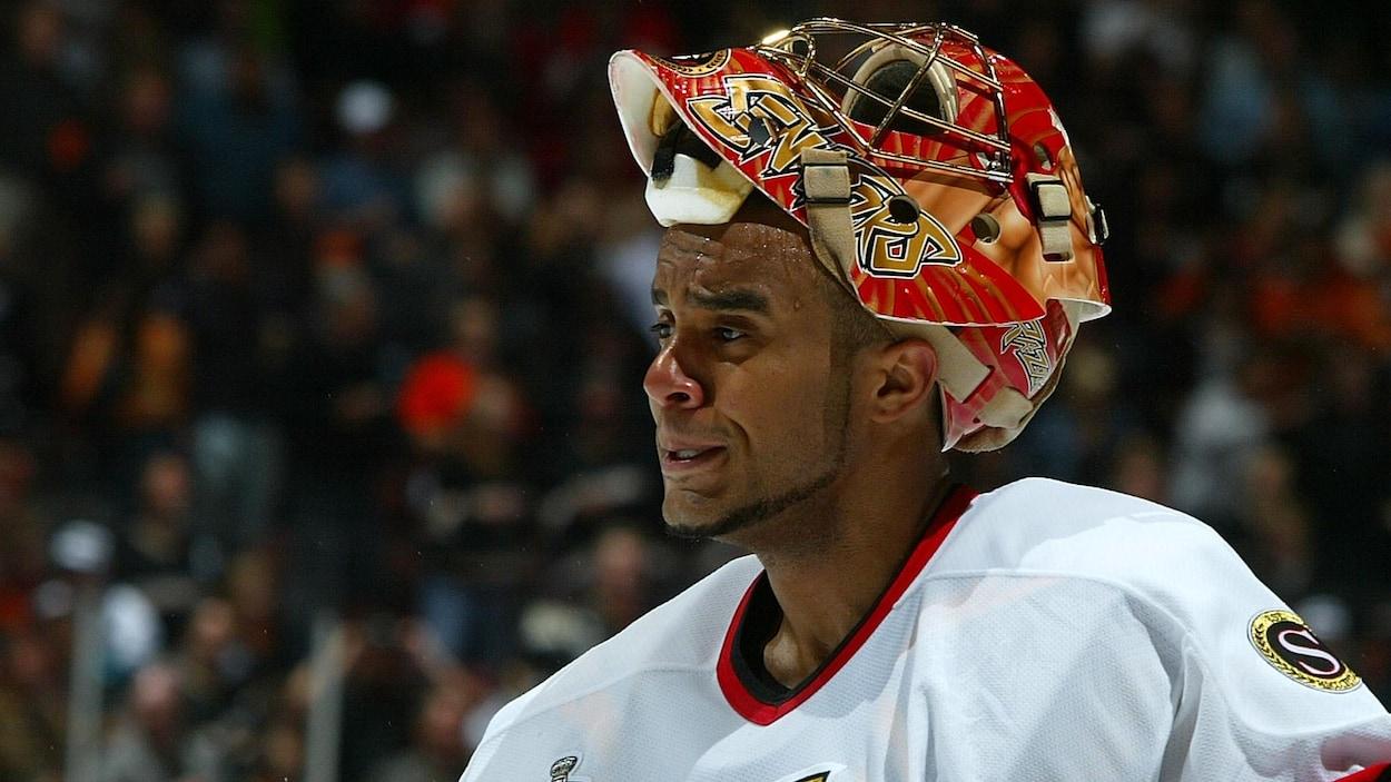 Le gardien se tient devant son filet avec son masque sur la tête.