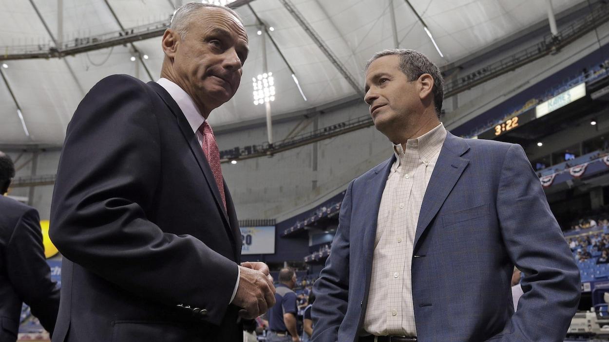 Le commissaire des ligues majeures et le propriétaire des Rays de Tampa Bay discutent avant un match de baseball.