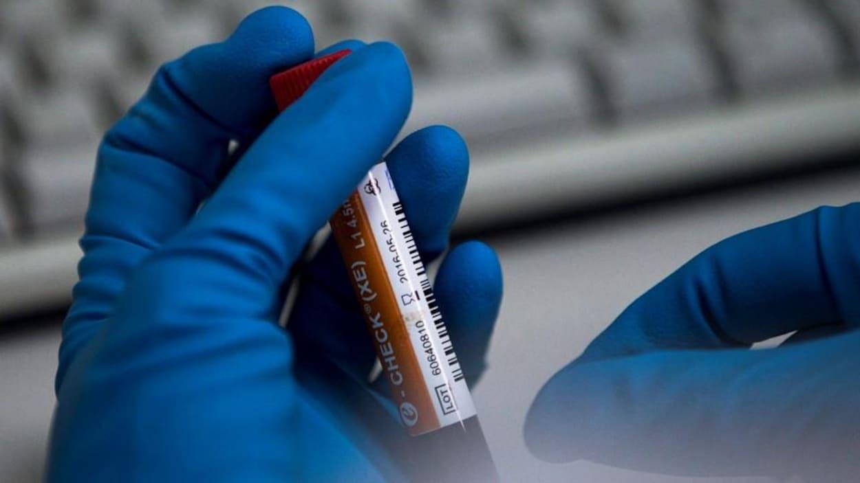 Une technicienne manipule l'éprouvette dans un laboratoire.