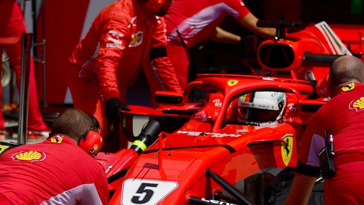 La voiture de Sebastian Vettel devant le garage Ferrari