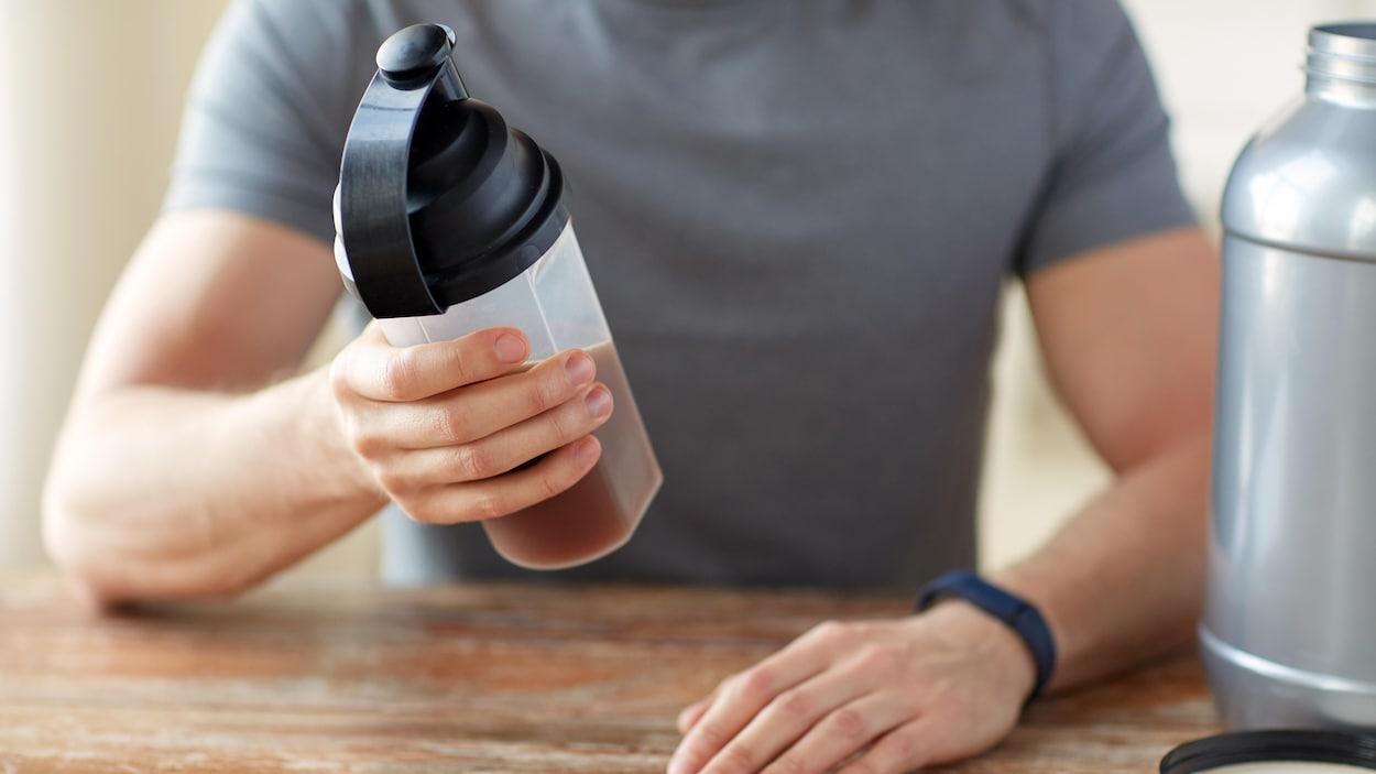 Un homme tient dans sa main une boisson sportive.