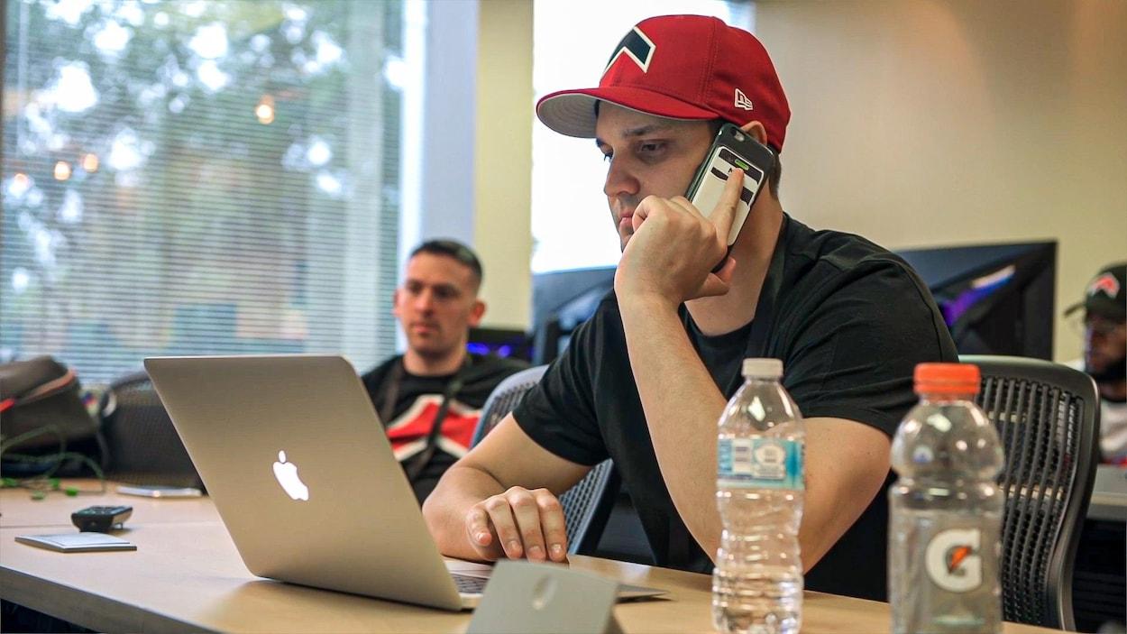 Shane Talbot discute au téléphone tout en travaillant à l'ordinateur.
