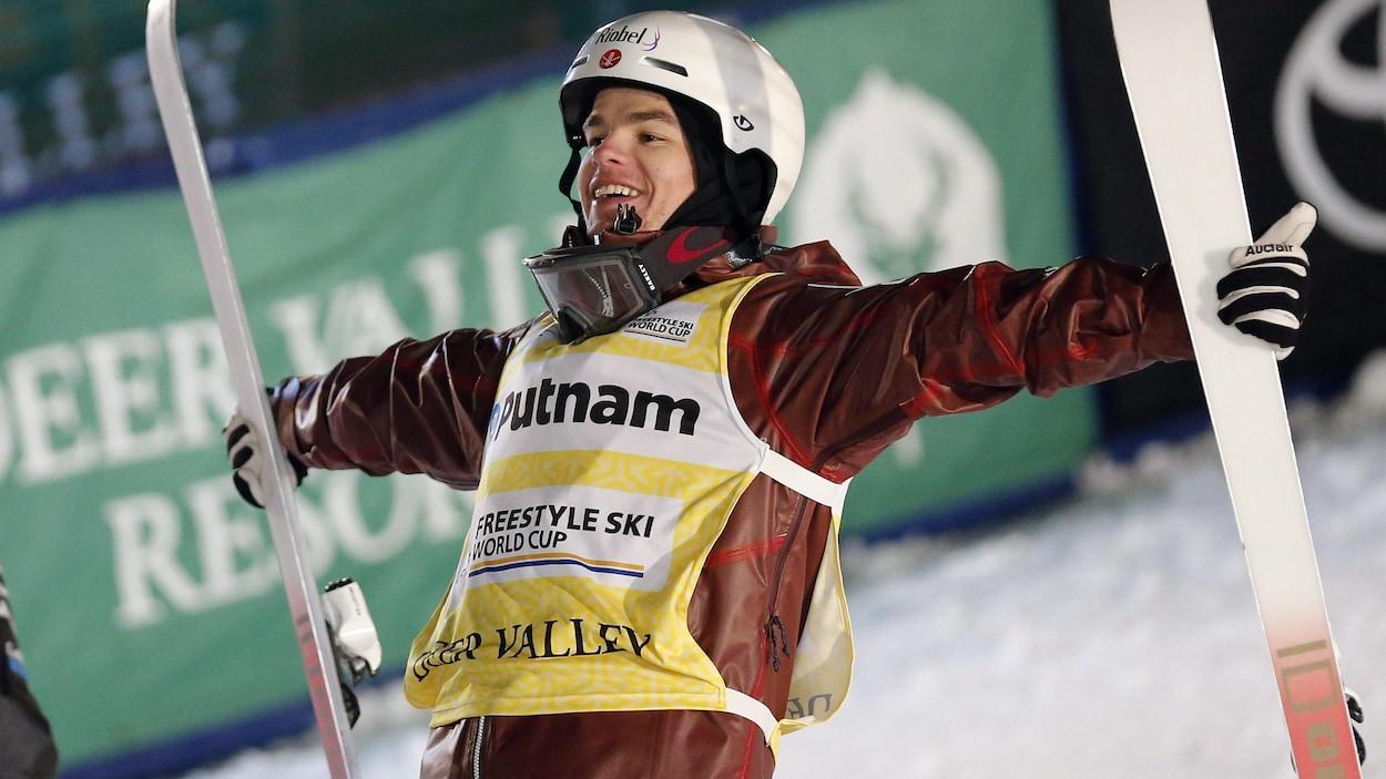 Le bosseur Mikaël Kingsbury, skis en mains, célèbre une autre victoire en Coupe du monde de ski acrobatique.