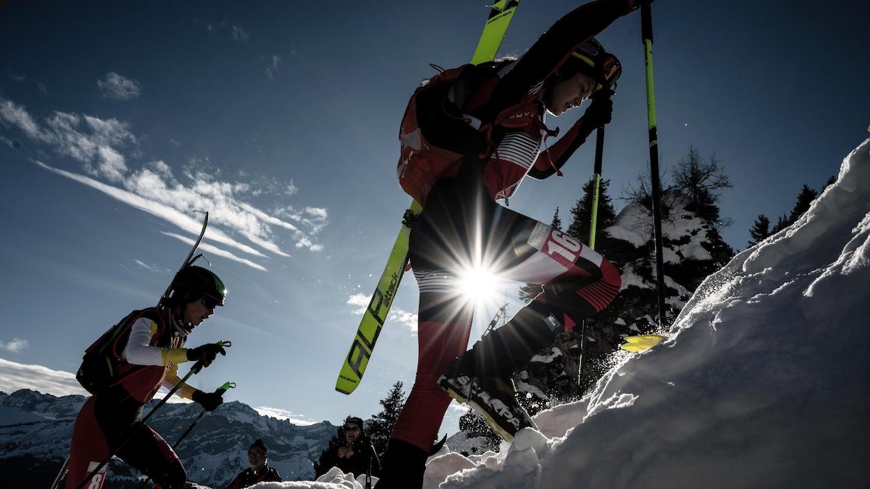 Deux skieuses montent une pente à pied.