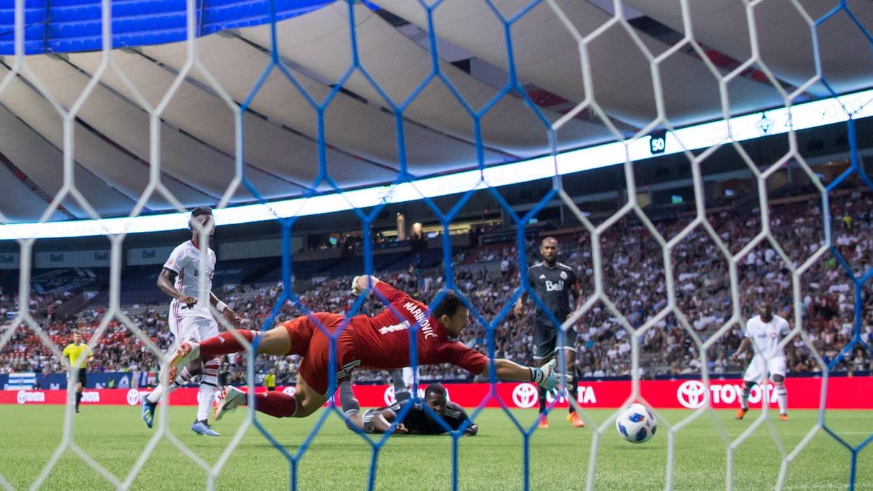 Un gardien tente d'arrêter le ballon en plongeant.