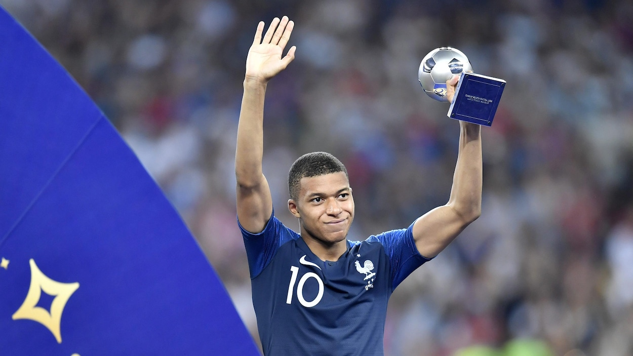 Le Français Kylian Mbappé soulève le trophée remis au meilleur jeune joueur de la Coupe du monde de 2018 après la victoire de son pays contre la Croatie en finale.
