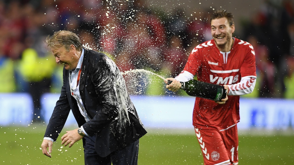 Nicklas Bendtner asperge de champagne son entraîneur Aage Hareide après la victoire du Danemark contre l'Irlande.