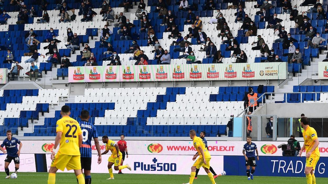 Des spectateurs éparpillés dans une tribune regardent un match de soccer.