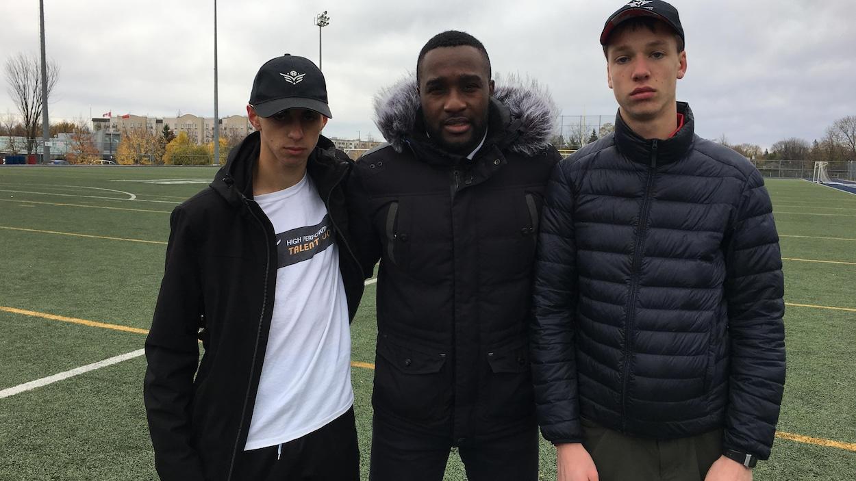 Les joueurs de soccer Nathan Bouassali et Thomas Topping posent pour la caméra en compagnie de leur entraîneur Marc Kamdem