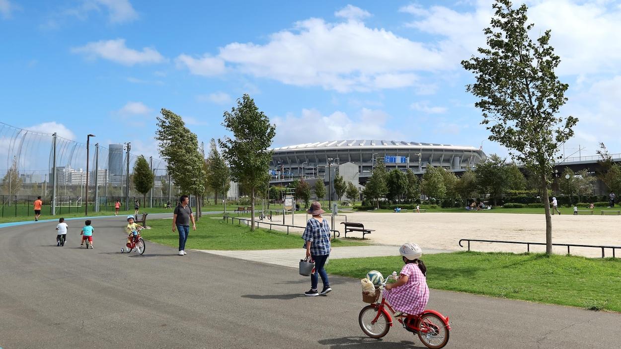 Des gens marchent devant un parc. Au loin, il y a un stade.