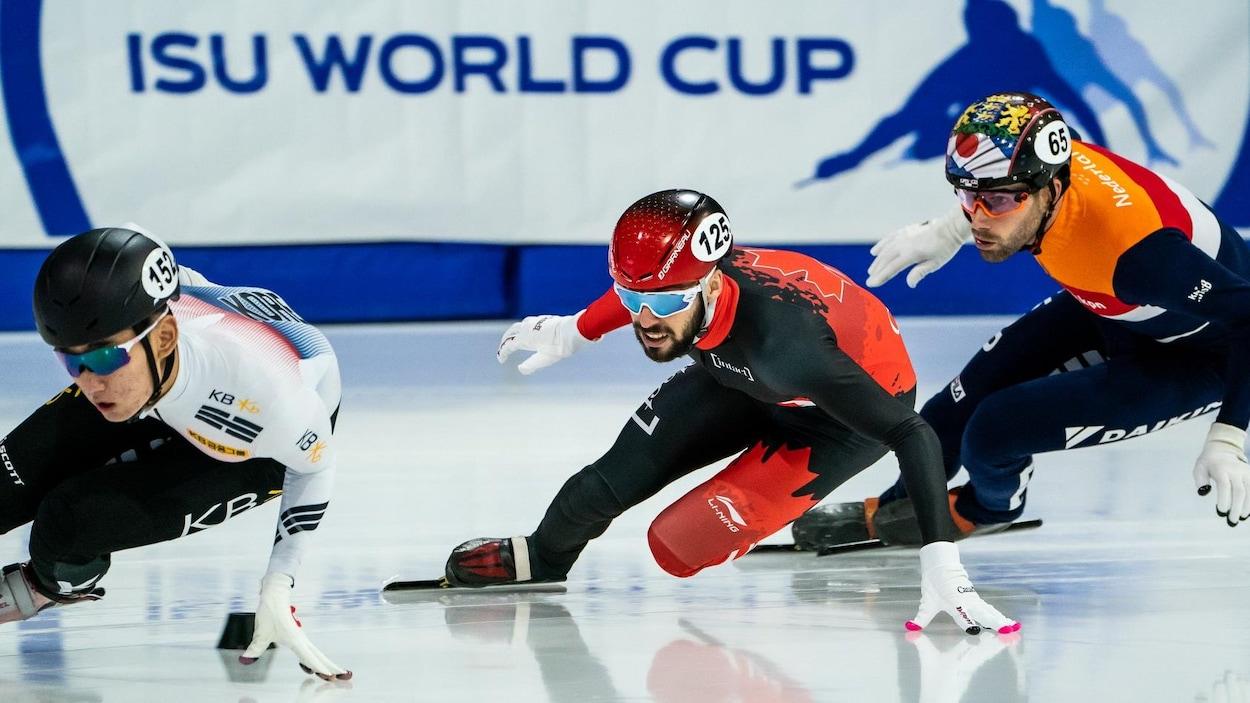 Des patineurs sortent d'un virage.
