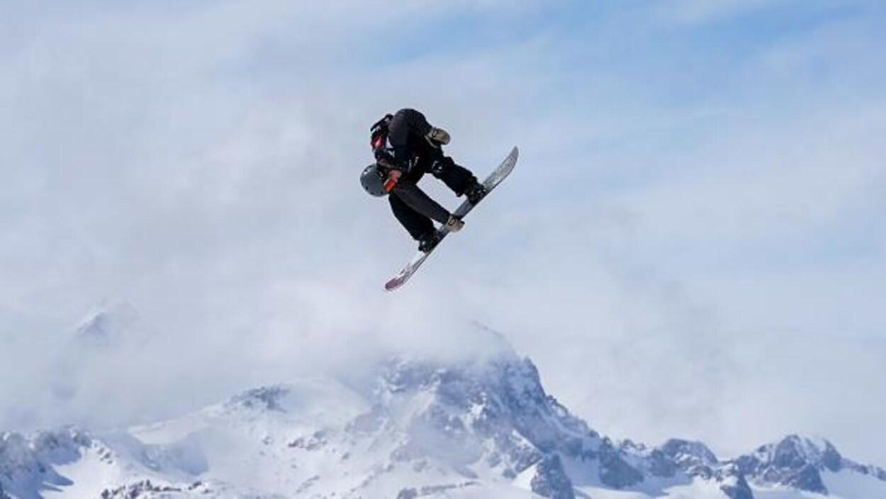 Pendant un saut, il tient le milieu de sa planche de la main droite.