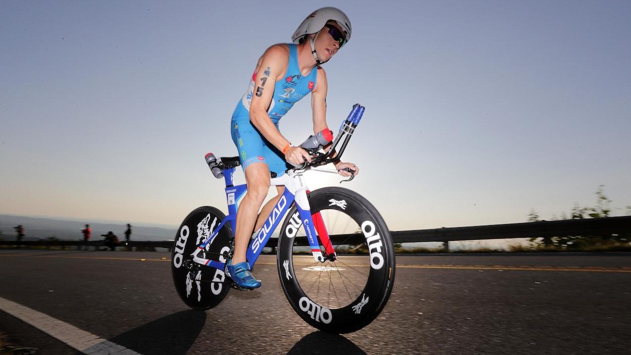 Il est en plein effort sur son vélo.