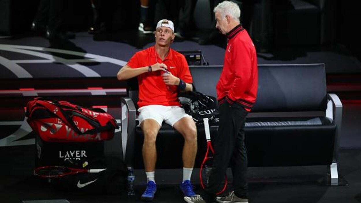 Le joueur canadien, assis sur une chaise, reçoit les conseils de son entraîneur américain.