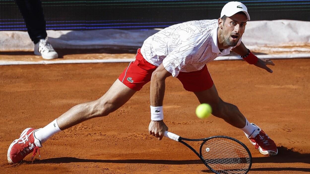 Il renvoie la balle du revers vers son adversaire, les jambes écartées.