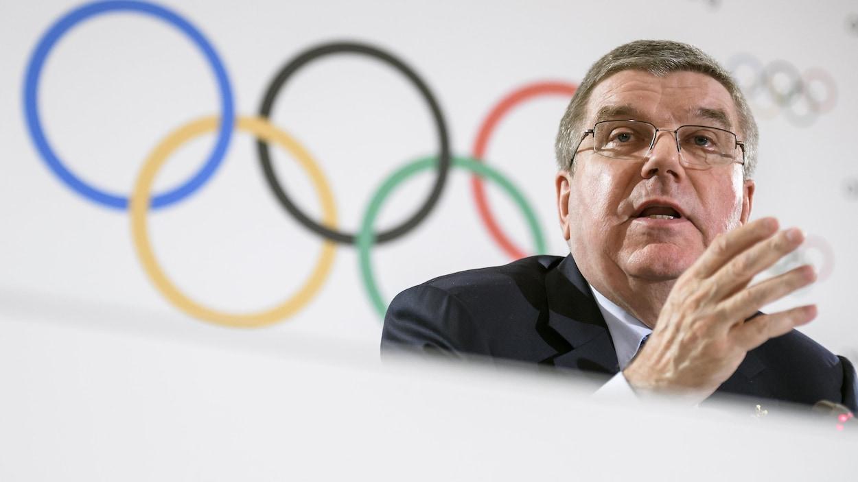Gros plan d'un homme en conférence de presse avec derrière lui les anneaux olympiques