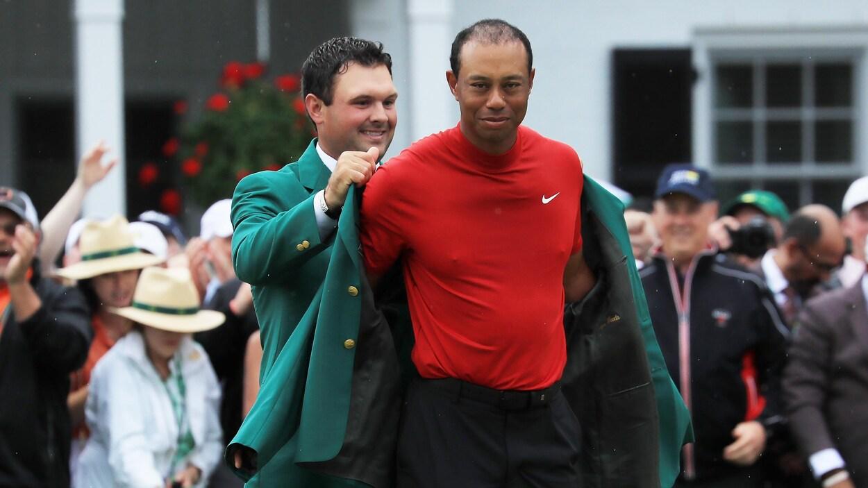 Tiger Woods reçoit son cinquième veston vert du champion en titre du Tournoi des maîtres, Patrick Reed