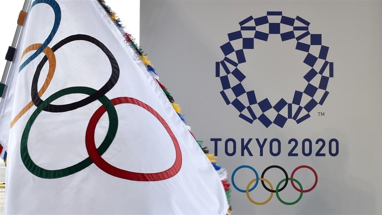 Le logo des Jeux de Tokyo à côté du drapeau olympique